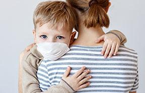 mom holding child wearing mask