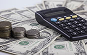 calculator and stacks of money